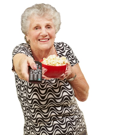 bowl of popcorn: portrait of senior woman holding pop corn bowl and changing channel of tv over white background