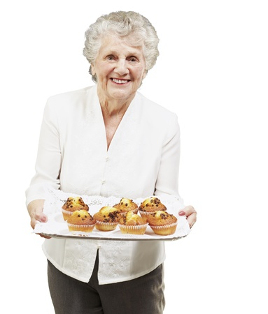 senior woman smiling and holding a tray with muffins against a white background photo