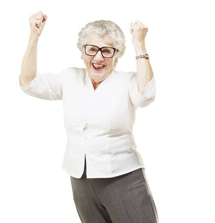 portrait of a cheerful senior woman gesturing victory over white background