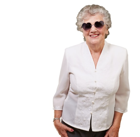 portrait of happy senior woman wearing heart glasses over white photo