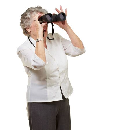portrait of senior woman looking through a binoculars over white background photo