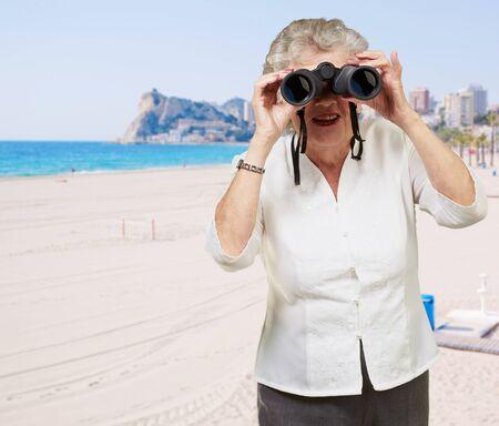 portrait of senior woman looking through a binoculars in the beach Stock Photo - 13608302