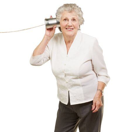 portrait of senior woman hearing with metal tin can over white background Stock Photo