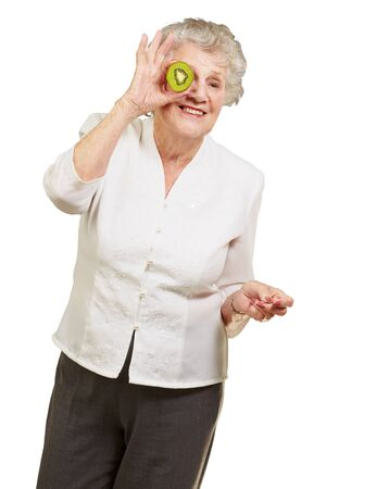 portrait of senior woman holding kiwi in front of her eye over white background photo