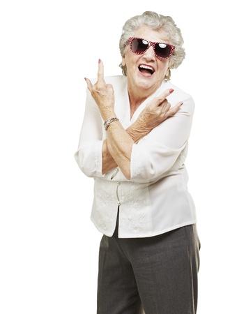 rock hand: Ritratto di donna senior facendo simbolo roccia su sfondo bianco