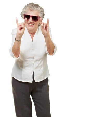 portrait of a happy senior woman doing rock symbol over white background photo