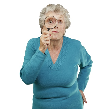 portrait of senior woman looking through a magnifying glass over white background Stock Photo - 13609810