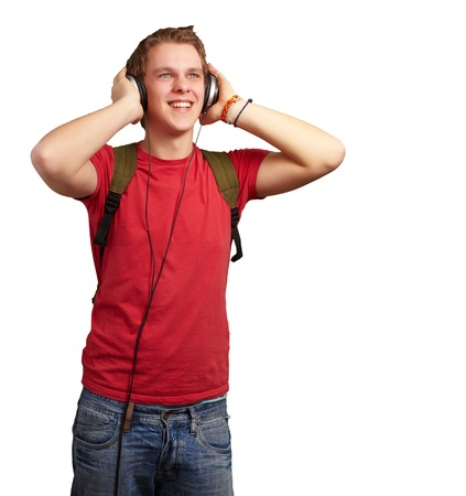 portrait of cheerful young student listening music with headphones over white photo
