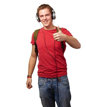 portrait of cheerful young student listening music and gesturing good with headphones over white photo