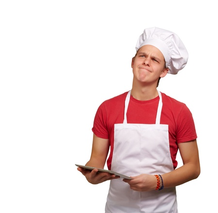 portrait of young cook man holding a digital tablet and thinking over white background photo