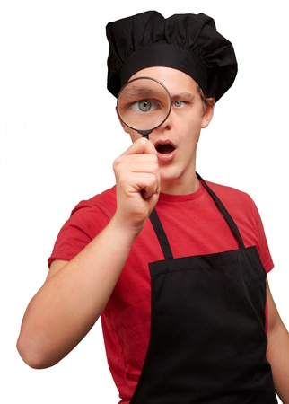 portrait of young cook man looking through a magnifying glass over white photo