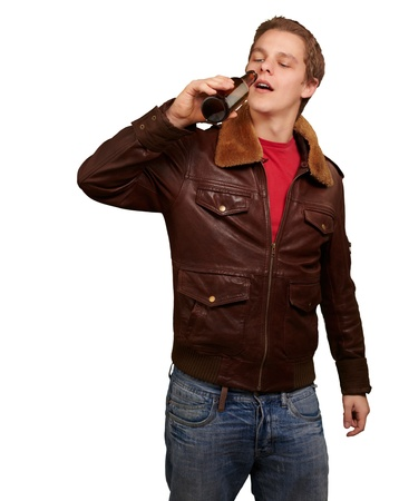 portrait of young man drinking beer against a white background photo