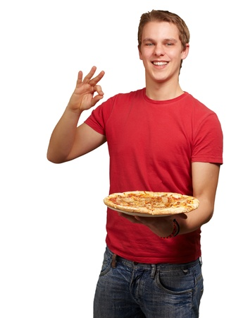 portrait of young man holding pizza and doing good gesture over white background photo