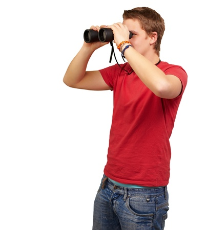 portrait of young man looking through a binoculars over white background photo