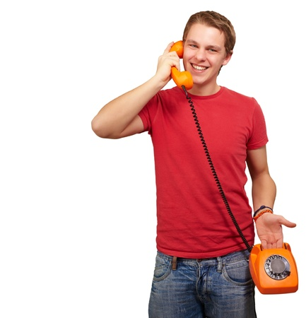 portrait of young man talking with vintage telephone over white background photo