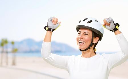 ciclista: retrato de un alegre deportivo mujer de mediana edad haciendo un símbolo de la victoria cerca de la playa