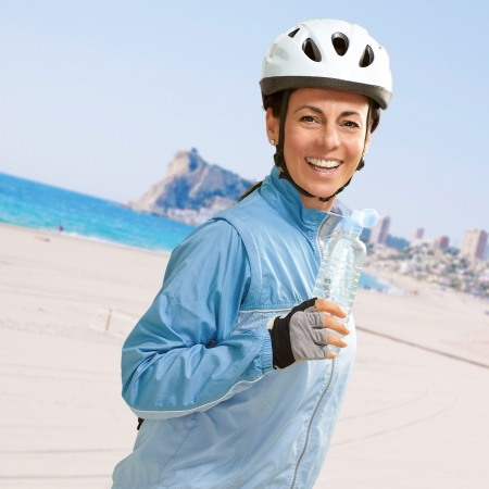 portrait of cyclist middle aged woman holding a water bottle in the beach photo
