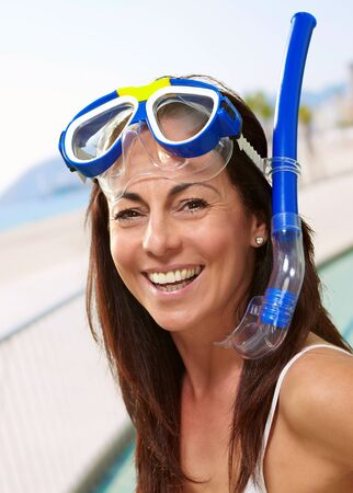 portrait of a happy middle aged woman wearing snorkel and goggles against the beach photo
