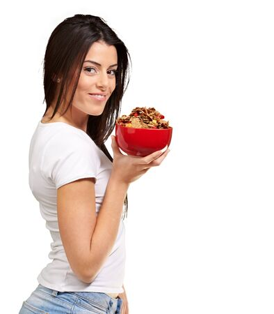 bowl of cereal: portrait of young woman holding a cereal bowl over white background