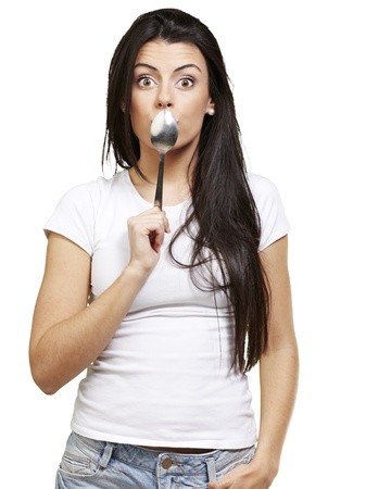 covering: woman covering her mouth with a spoon against a white background
