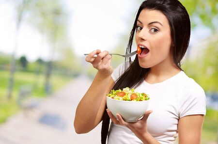 portrait of young woman eating salad at park Stock Photo - 13607842