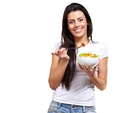 portrait of healthy woman eating salad against a white background