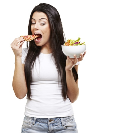 woman choosing a slice of pizza instead of a salad against a white background