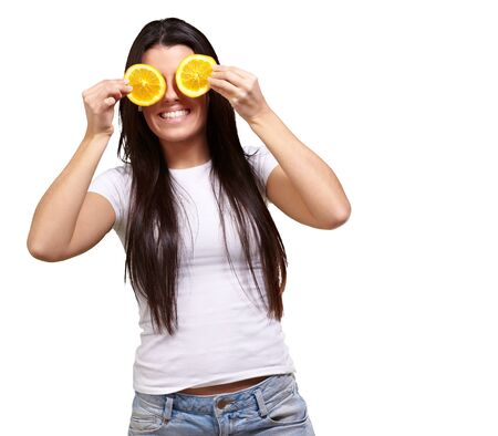 portrait of young woman holding orange slices in front of her eyes over white background photo
