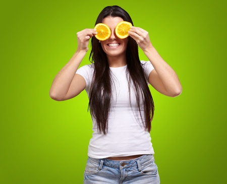 portrait of young woman holding orange slices in front of her eyes over green background photo