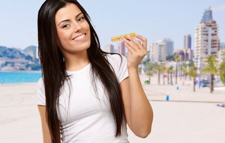 portrait of young woman eating cereal bar against a beach photo