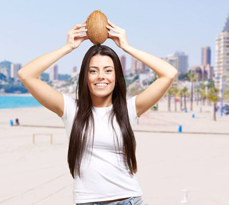 portrait of young woman holding coconut against the beach photo