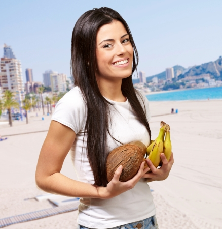 portrait of young woman holding tropical fruit near the beach photo