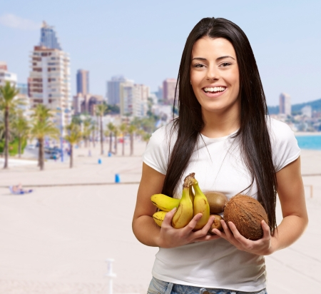 portrait of young woman holding tropical fruits against the beach photo