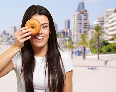 portrait of young woman holding donut in front of her eye against the beach Stock Photo - 13607114