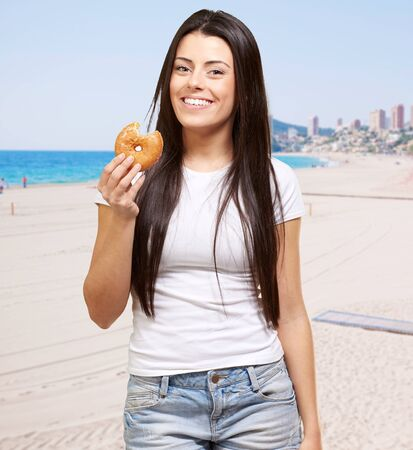 portrait of young woman holding donut against the beach Stock Photo - 13609947