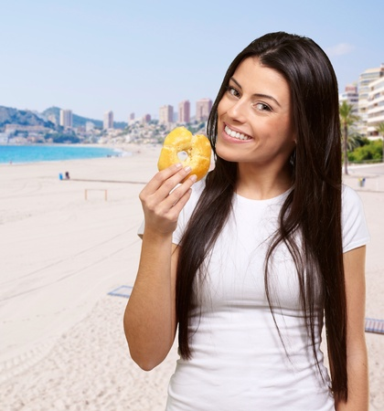 portrait of young woman holding donut against the beach Stock Photo - 13609851