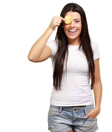 portrait of young woman holding a potato chip in front of her eye over white photo