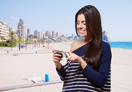 portrait of young woman touching a modern mobile against the beach photo