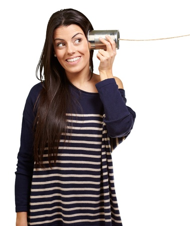 tin can telephone: Young woman hearing using a metal tin can over white background
