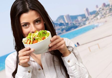portrait of young woman holding a fresh salad against a beach Stock Photo - 13607863