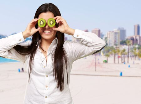 portrait of young girl holding kiwi slices in front of her eyes against a beach photo