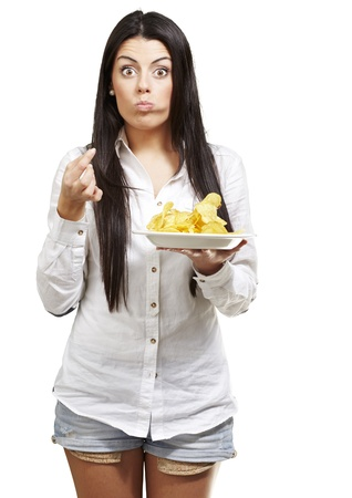 young woman eating potatoe chips against a white background