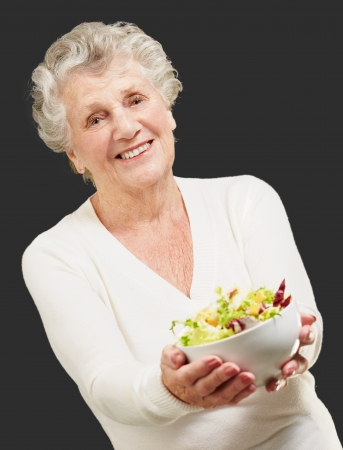 old people eating: portrait of senior woman showing a fresh salad over black background Stock Photo