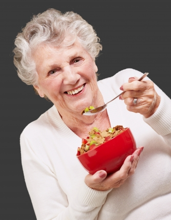 portrait of senior woman holding a cereals bowl against a black background Stock Photo - 13844688
