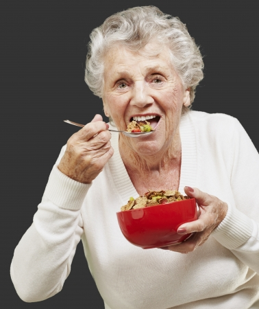 senior woman eating cereals out of a red bowl against a black background photo