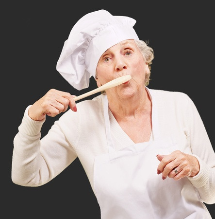 over black: portrait of cook senior woman with wooden spoon on mouth over black