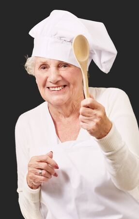 portrait of senior cook woman holding a wooden spoon over black background photo