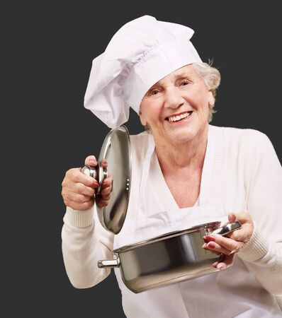 portrait of cook senior woman opening sauce pan over black photo