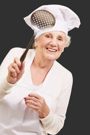 portrait of sweet senior cook woman holding a metal spoon over black photo