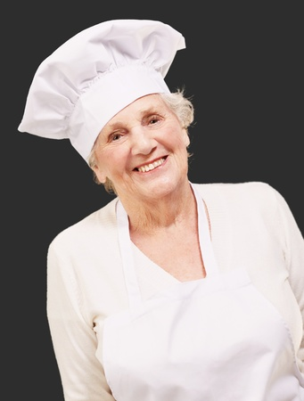 portrait of cook senior woman smiling over black background photo
